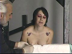 young tattooed brunette gets her nips and tits tortured with needle play